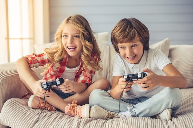 Bonita niña y niño están jugando consola de juegos. Foto Premium