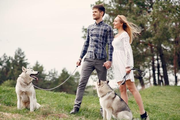 Bonita pareja en un bosque de verano con perros. Foto gratis