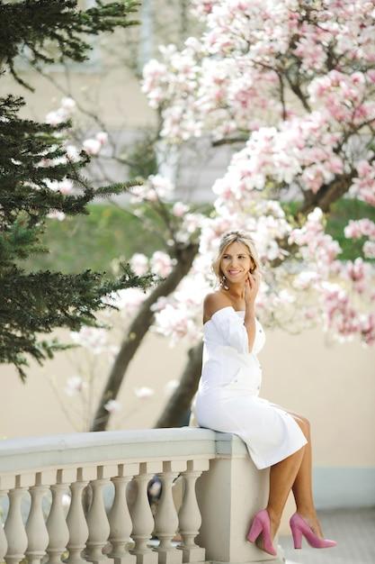 Una bonita rubia se sienta en una valla decorativa blanca Foto gratis