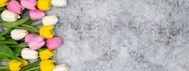 Bonito banner para el encabezado de su sitio web hecho con tulipanes en una piedra Foto gratis