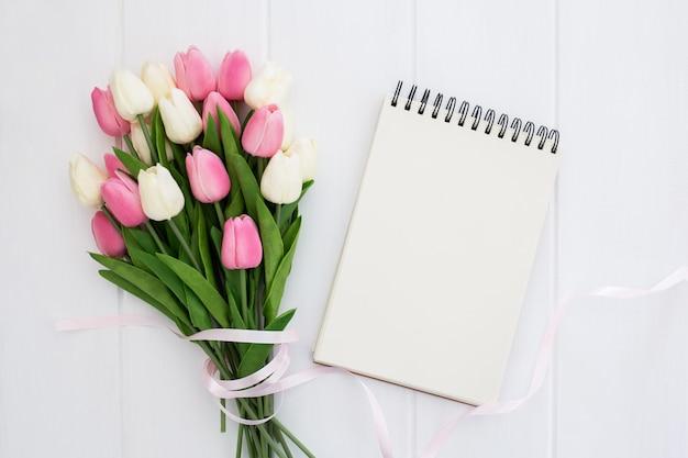 Bonito ramo de flores de tulipanes con cuaderno vacío. Foto gratis