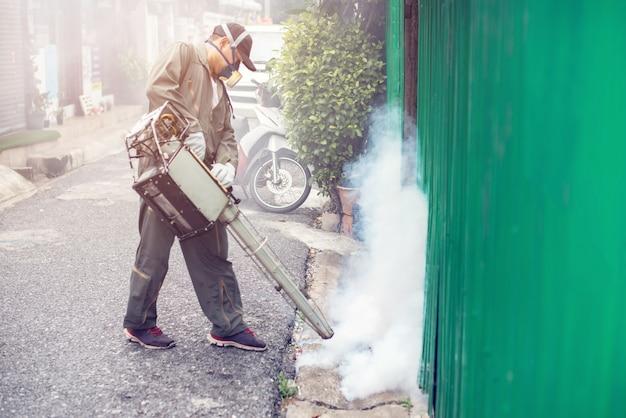 Borrosa del trabajo del hombre empañándose para eliminar el mosquito. Foto Premium
