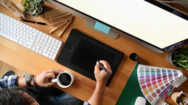 Bosquejos jovenes del dibujo del diseñador en la tableta gráfica digital en el estudio. vista superior tiro Foto Premium