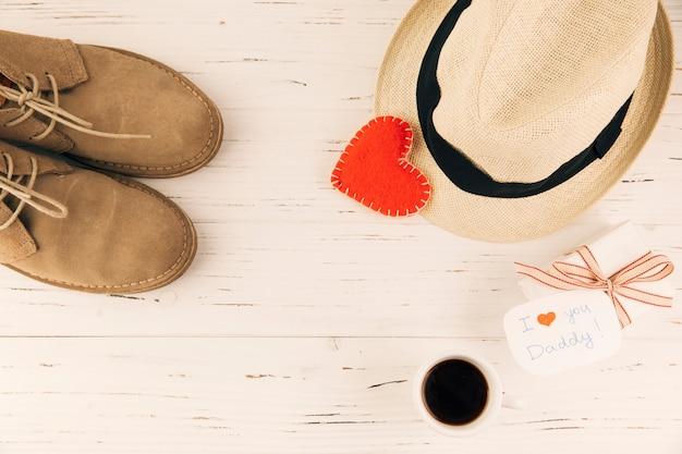 Botas cerca de sombrero con corazón y presente. Foto gratis