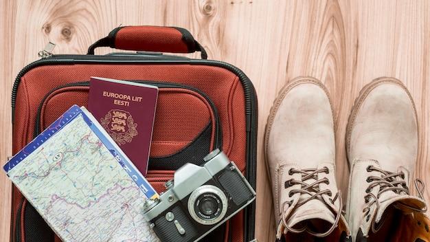 Botas cerca de suministros turísticos y maleta Foto gratis
