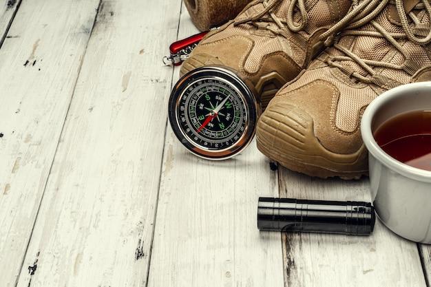 Botas de montaña, brújula y cuchillo. senderismo equipo al aire libre Foto Premium