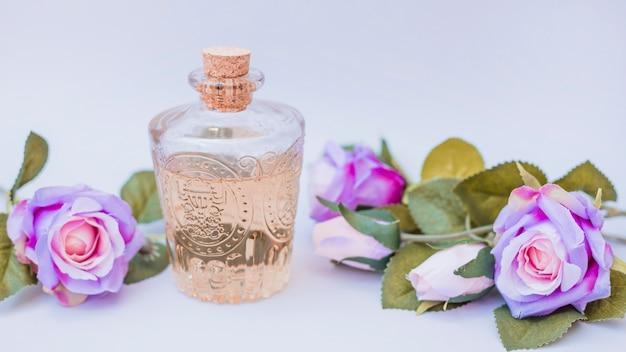 Botella de aceite esencial y flores falsas en superficie blanca Foto gratis