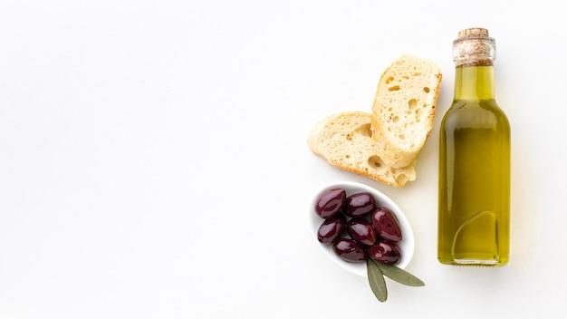 Botella de aceite de oliva rebanadas de pan y aceitunas moradas con espacio de copia Foto gratis