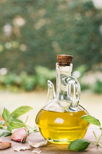 Botella de aceite de oliva transparente al aire libre Foto gratis