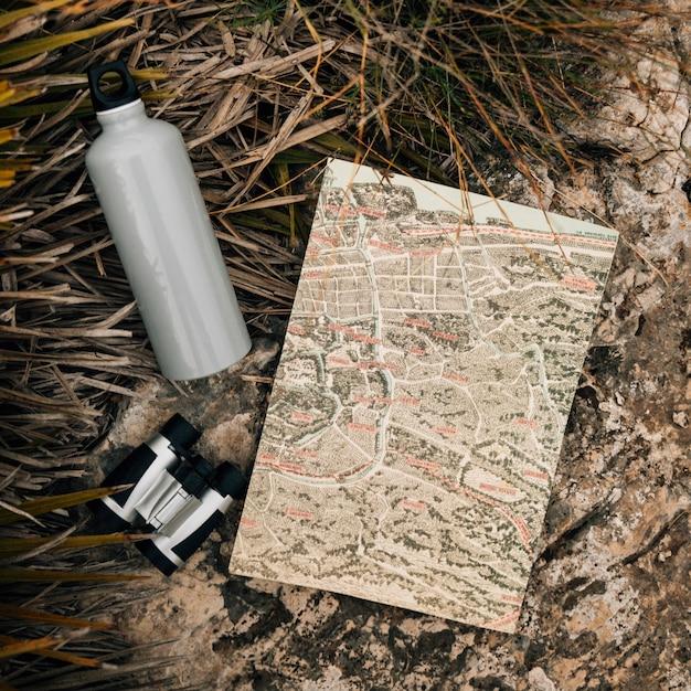 Botella de agua; binoculares y mapa en roca cerca de la hierba Foto gratis