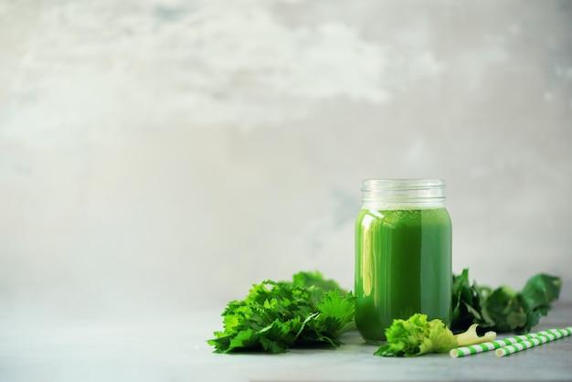 Botella de batido de apio verde sobre fondo de hormigón gris Foto Premium