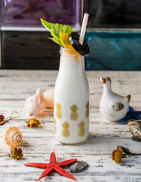 Una botella de batido con conchas de mar. Foto gratis