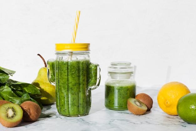 Botella de batido verde con fruta fresca. Foto gratis