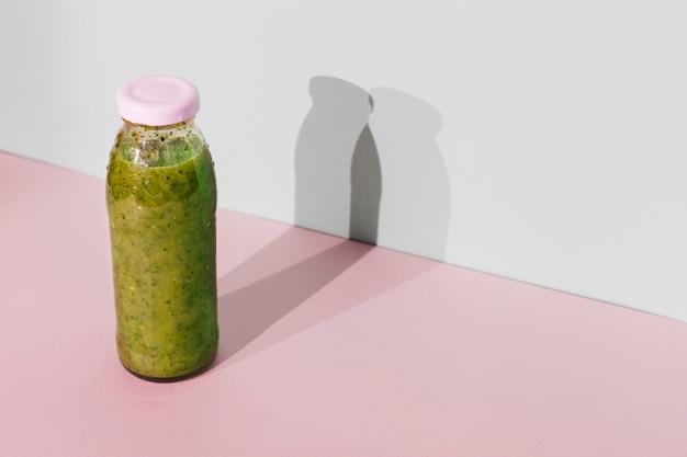 Botella de batido verde en la mesa Foto gratis