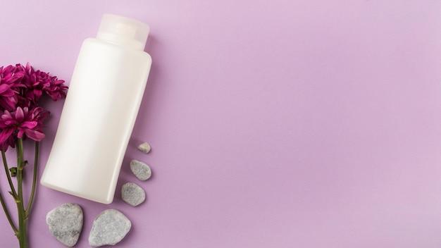 Botella blanca cerrada con flores rosas y piedras de spa sobre fondo rosa pastel Foto gratis