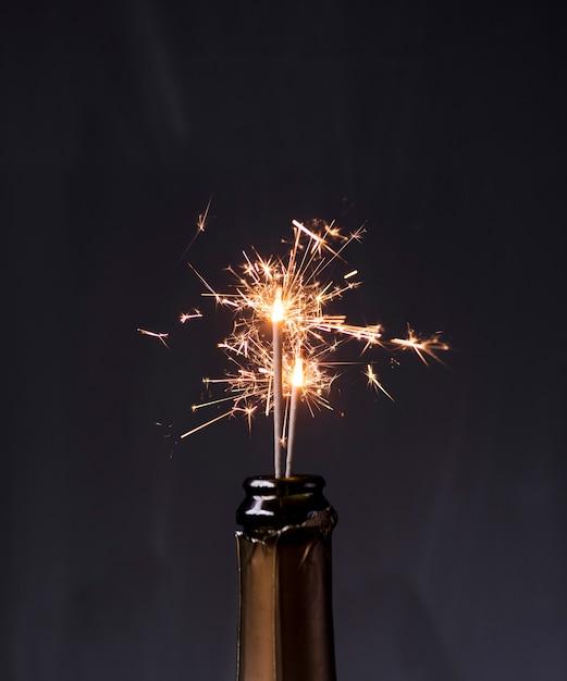 Botella de champagne con bengalas sobre fondo negro Foto gratis