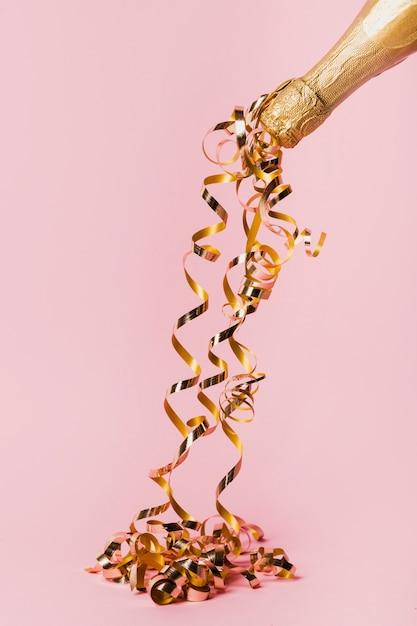 Botella de champagne y cintas doradas. Foto gratis