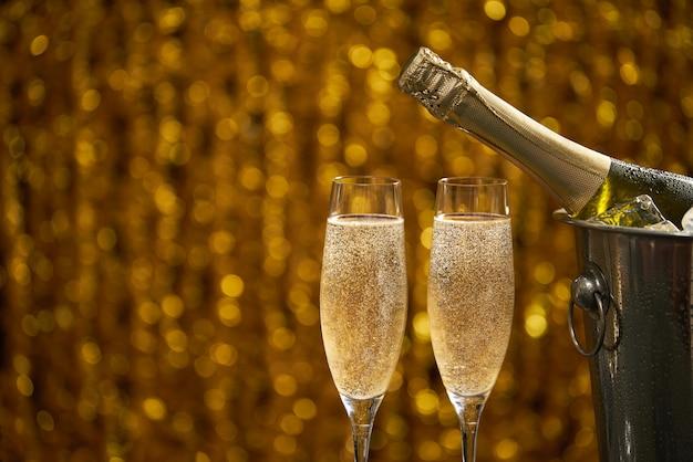 Botella de champagne en un cubo con hielo y dos copas de champagne sobre fondo dorado bokeh Foto Premium