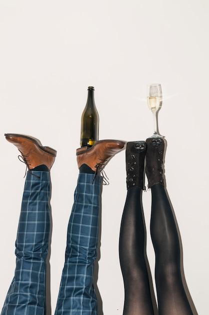 Botella de champán y copa en los pies. Foto gratis