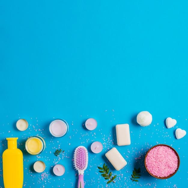 Botella de champú; crema; jabón; bomba de baño con sal rosa sobre fondo azul Foto gratis