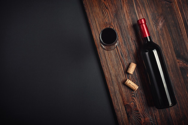 Botella de corchos de vino y copa de vino sobre fondo oxidado Foto Premium