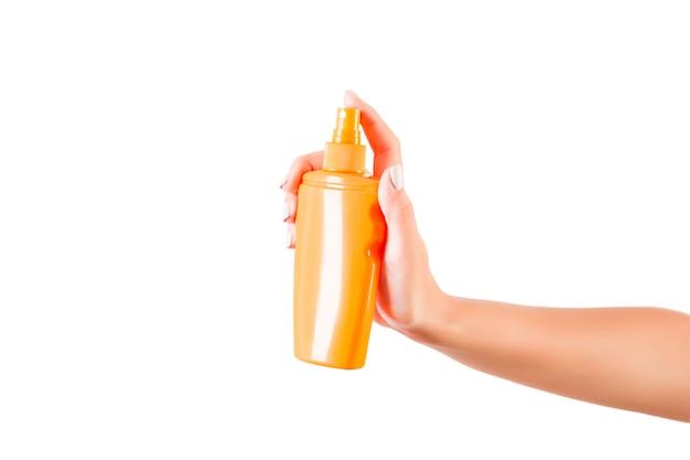 Botella de crema de explotación de mano femenina Foto Premium