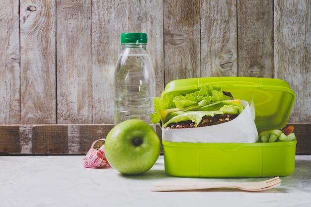 Botella de agua y manzana junto a una fiambrera Foto Gratis