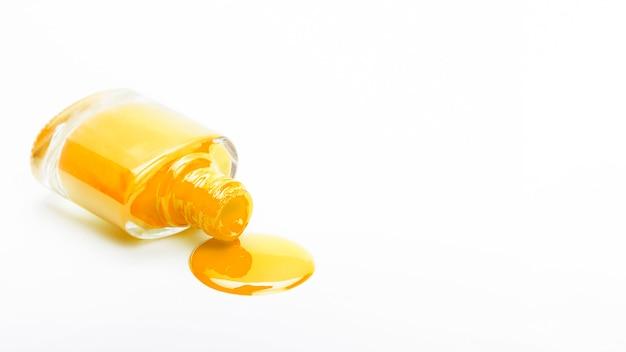 Botella de esmalte de uñas caído amarillo sobre fondo liso Foto Premium
