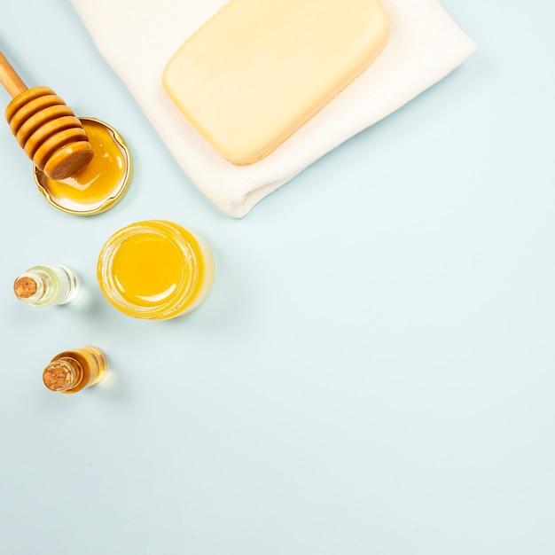 Botella de jabón y aceite esencial con miel sobre fondo liso Foto gratis