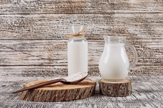 Botella de leche con jarra de leche sobre una rodaja de madera, cuchara de madera vista de ángulo alto sobre un fondo blanco de madera Foto gratis