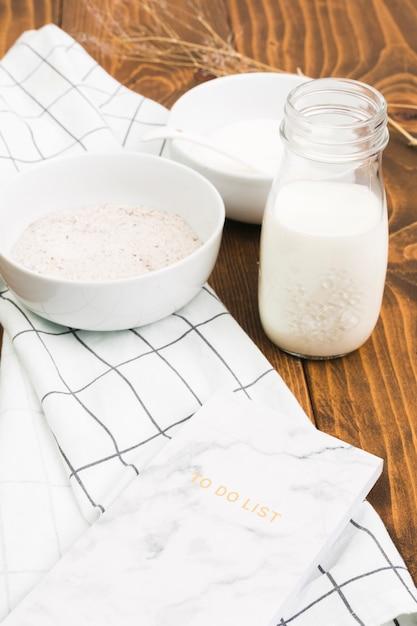Botella de leche saludable; tazón de harina y hacer lista sobre panel de madera. Foto gratis