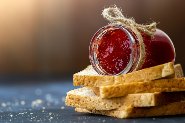 La botella de mermelada de fresa y el pan integral se apilan sobre un fondo negro Foto Premium