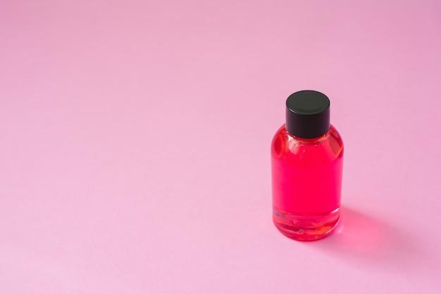 Botella de producto cosmético rosa con tapa negra para cosméticos para el cuidado de la piel corporal o cabello sobre fondo rosa. Foto Premium