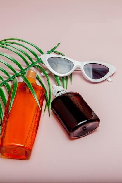 Botella de protector solar. el concepto del resort en el mar, horario de verano. vista superior, plano, minimalismo Foto Premium