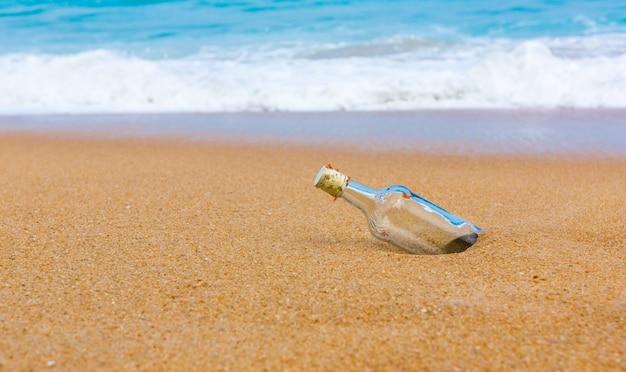 Botella vacía en la orilla de la playa Foto gratis