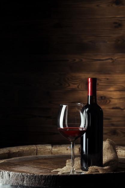 Botella y vaso de vino tinto en barril de madera con fondo de madera oscura Foto Premium