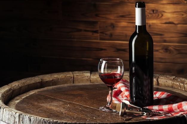 Botella y vaso de vino tinto en barril de madera Foto Premium