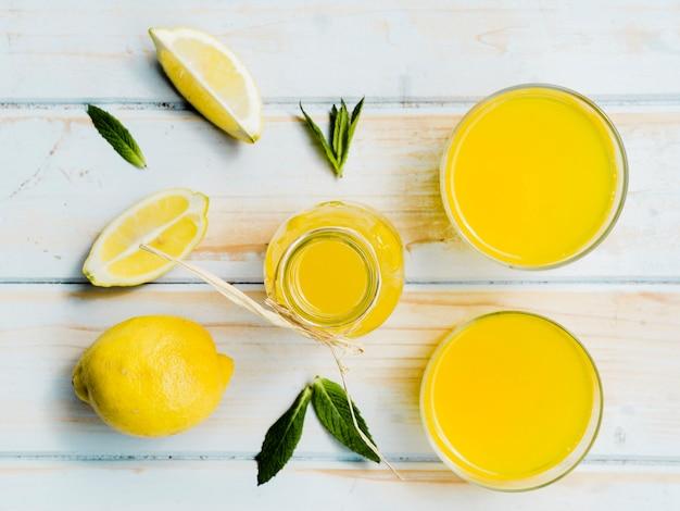 Botella y vasos de bebida amarilla con limón fresco y menta. Foto gratis