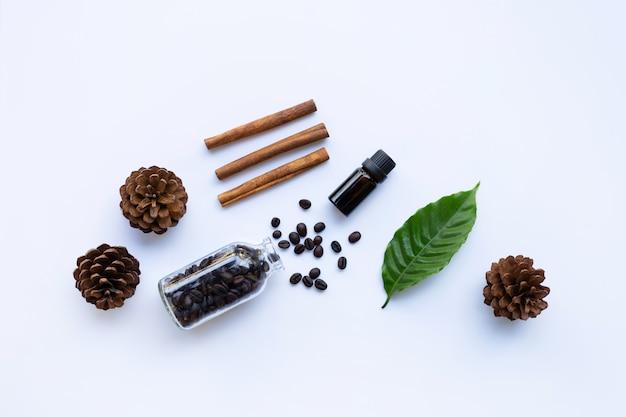 Botella de vidrio de aceite esencial de café y canela en blanco Foto Premium