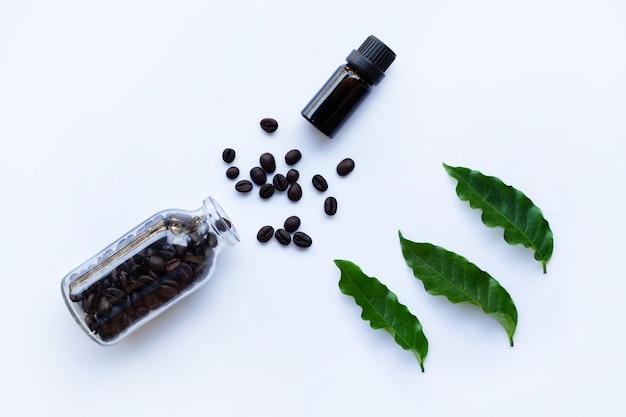 Botella de vidrio con aceite esencial de café y granos de café en blanco Foto Premium