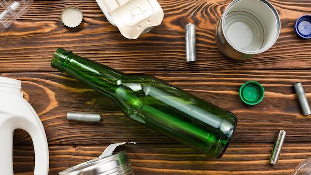 Botella de vidrio vacía al lado de varios residuos Foto gratis