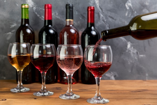 Botella de vino llenando copa Foto gratis