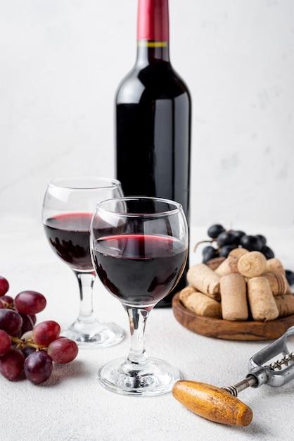 Botella de vino tinto de alto ángulo y copas con vino Foto Premium