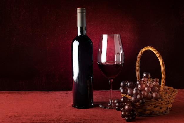 Botella de vino tinto y copa con cesta de uvas Foto gratis