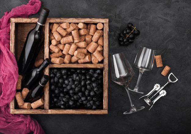 Botella de vino tinto de lujo y vasos vacíos con uvas oscuras con corchos y sacacorchos dentro de la caja de madera vintage. Foto Premium