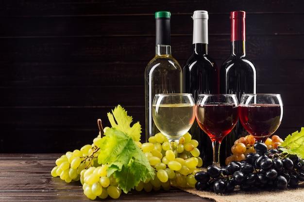 Botella de vino y uva en mesa de madera Foto Premium