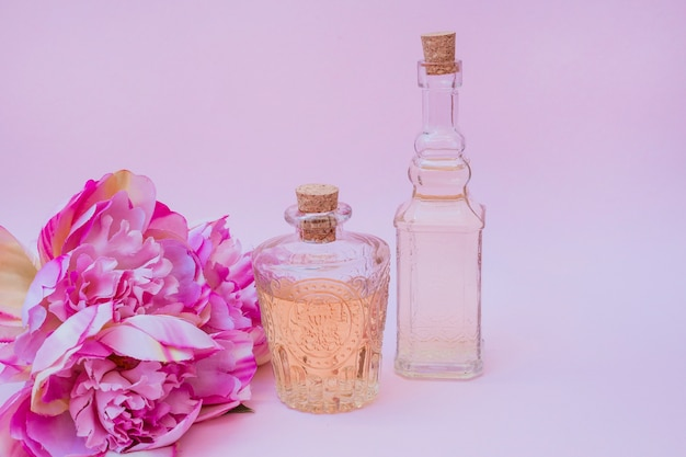 Botellas de aceite esencial y flores sobre fondo rosa Foto gratis