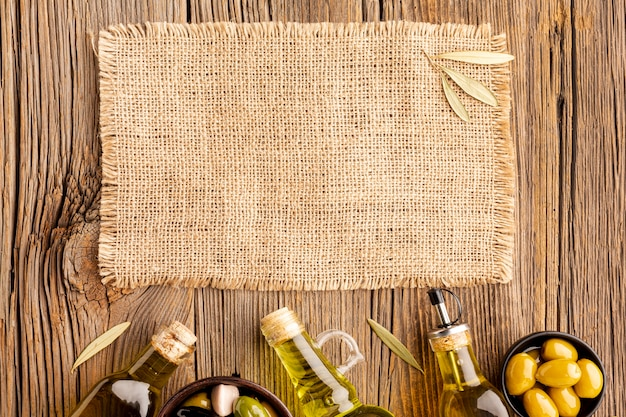 Botellas de aceite de oliva con aceitunas y maqueta textil Foto Premium