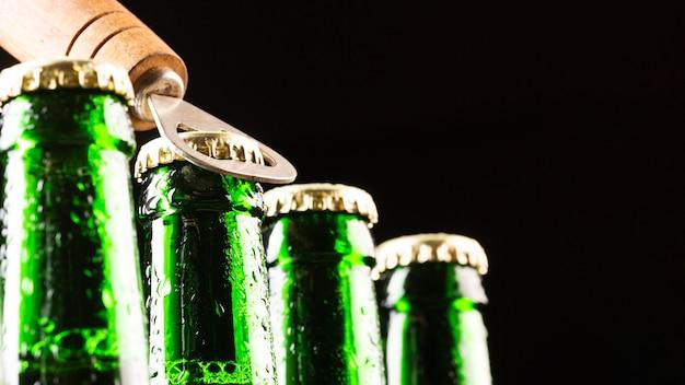 Botellas de cerveza y un abridor Foto gratis