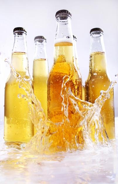 Botellas de cerveza con salpicaduras de agua. Foto gratis